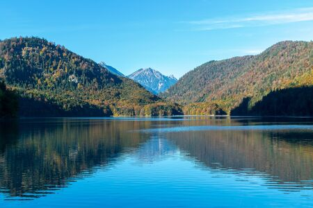 Symmetric reflection of the Alps and the shores in the water surface in the lake in autumn