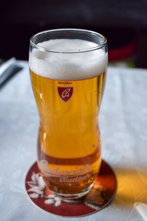 PRAGUE, CZECH REPUBLIC - OKTOBER 11, 2018: Glass of light beer with foam on stand on the table in restaurant