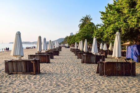 Flat rows of folded beach umbrellas and sunbeds on the sandy seashore in tropics