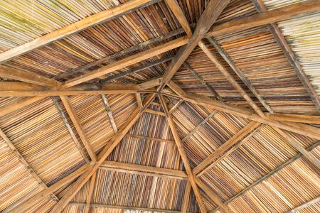 Mounting straw umbrella from below with wooden beams