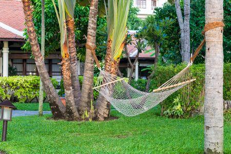 Hammock under palm trees on beach in the tropics on vacation Standard-Bild - 140373233