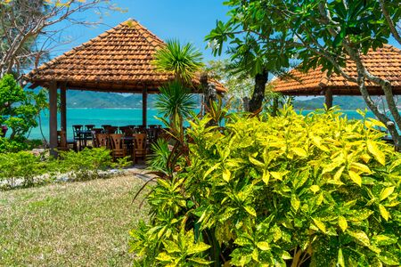 Wooden canopy with wooden chairs by the sea in the tropics with tropical bushes