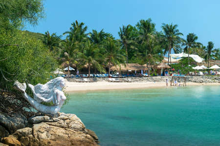 NHA TRANG, VIETNAM - APRIL 19, 2019: Sculpture of a mermaid on beach and thatched houses on sand in the tropics