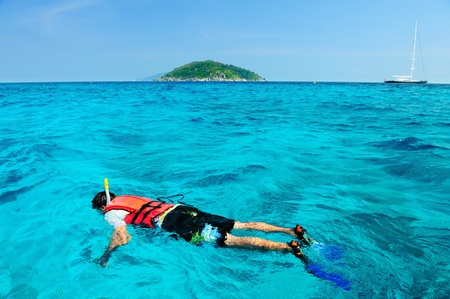 a man snorkling around the island in south of Thailand photo