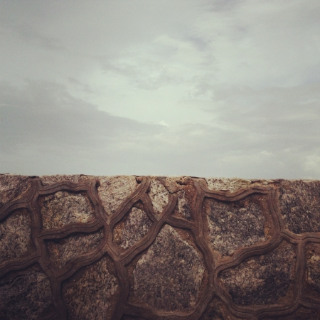 Stone wall against a cloudy sky photo
