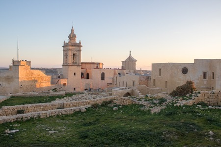 Panoramic view on old, historical St. Joseph's Chapel inside Citadel of Victoria surrounded by antique ruins, walls with grass field and sandstones in the foreground. Gozo, Malta in the background.