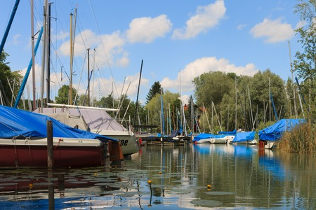 Nice view on Harbor with many boats, piers and water plants. W?rthsee in Bachern. Many different ships for water sports are ready. Taken from Kayak on a sunny day. Woerthse, Starnberg. Bavaria.