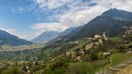Panoramic view on Tyrol Castle with Castle Brunnenburg inside Valley and Alps of Meran. Tirol Village, Province Bolzano, South Tyrol, Italy.