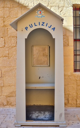 Detail view on a traditional and old maltese wooden police lodge. In the Background a sandstone wall. Reklamní fotografie