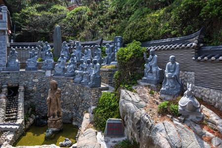 Panoramic view on many religious buddhist statue of praying monks in the korean Haedong Yonggungsa Temple. Busan, South Korea, Asian. 写真素材