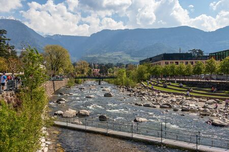 View on River Passer with Promenade, vegetation and around Buildings in Meran. Province Bolzano, South Tyrol, Italy. Europe.