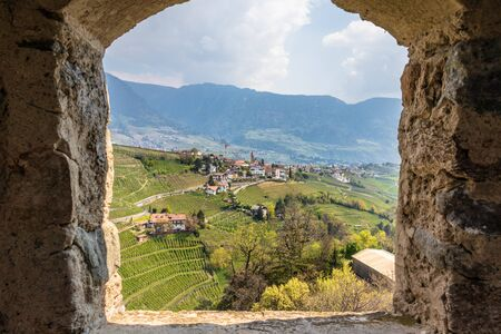 Village Tyrol, Dorf Tirol im Meraner Land, with wine plantations and Alps in background. Framed by the window of Castle Tyrol. South Tyrol, Italy