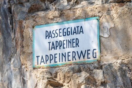 Bilingual signpost of Tappeinerweg in german and italian, Passeggiata Tappeiner, on a stonewall. Merano. Province Bolzano, South Tyrol, Italy.