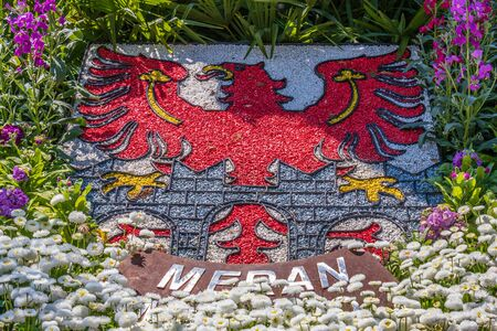 Detail view on Natural Crest, Emblem, Flag of City Meran in flowerbed. Merano. Province Bolzano, South Tyrol, Italy. Europe.