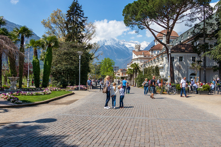 Street scenario on Passer Promenade in Meran with Alps Mountains in the background. Merano. Province Bolzano, South Tyrol, Italy. Europe. Redactioneel