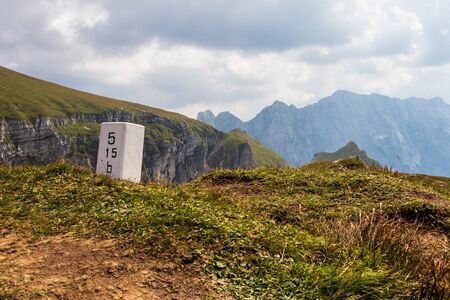 Border Stone between Slovenia and Italy on the top of Mangart Saddle, Mangartsko sedlo. near Mangart Road. Julian Alps in background. Stockfoto