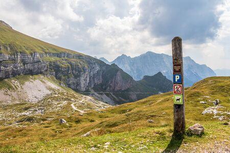 Sign of Triglav National Park with hints on top of Mangart Saddle, Mangartsko sedlo. Mangart Road, Mangartska cesta, in background. Bovec, Slovenia