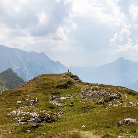 Person alone around Alps between huge Mountain Chains inside beautiful Nature. Summer Day Panorama in Julian Alps, Triglav National Park, Slovenia. Stockfoto