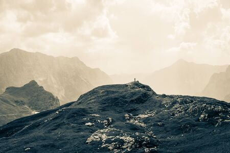 Woman alone on Summit between huge Mountain Chains inside beautiful Nature. Summer Day Panorama. Julian Alps, Triglav National Park, Slovenia.