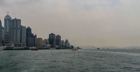 Skyline Panorama with Victoria Bay, Star Ferry and Islands on the horizon. Taken from Kowloon. Hong Kong, China, Asia