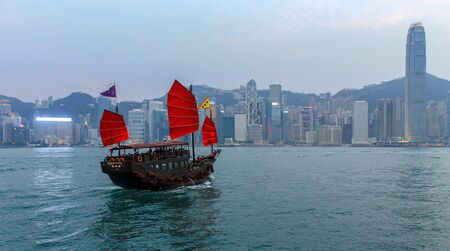 Skyline Panorama with Victoria Bay and a traditional wooden chinese-style Sailing Boat. Taken from Kowloon. Hong Kong, China, Asia