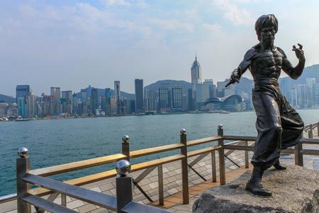 Bruce Lee Statue on Avenue of Stars near the promenade and the Skyline of Hongkong in background. Tsim Sha Tsui, Hong Kong, China.