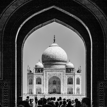 Silhouette of Taj Mahal through the Great Gate entrance with people. UNESCO World Heritage in Agra, Uttar Pradesh, India