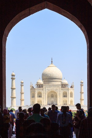 View on Taj Mahal through the Great Gate entrance with tourists. UNESCO World Heritage in Agra, Uttar Pradesh, India