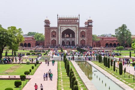 Great Entrance Gate with walkway, garden square, reflecting pool and visitors taken from Taj Mahal. Agra, Uttar Pradesh, India Редакционное