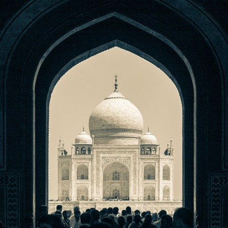 Silhouette of Taj Mahal through the Great Gate entrance with many tourists. UNESCO World Heritage in Agra, Uttar Pradesh, India
