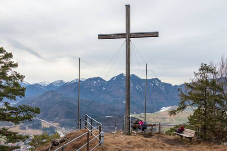 Panorama of Heldenkreuz and viewpoint Platform with resting Hikers in Bavarian Prealps, Eschenlohe, Upper Bavaria, Germany