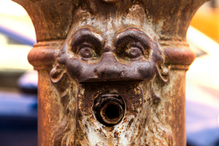 An old metal well in the shape of a human face, the crane emerges from the mouth of a man, an ancient well