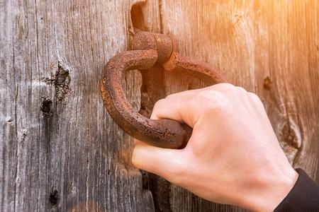 Campana vieja en la puerta, la mano toca la puerta de madera Foto de archivo