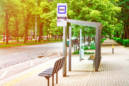 an empty bus stop in the center of the city is lit by the sun, a stop against the background of green trees Banque d'images - 101736633