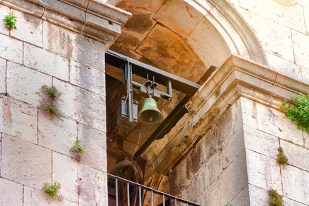 Ancestral bell tower and a bell in an old church, a church illuminated by the sun 版權商用圖片