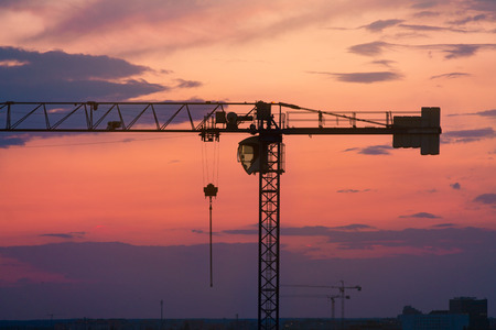 Construction crane against the sky, sunset, cityscape Stock Photo