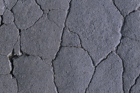 Cracked painted asphalt making abstract background. cracks on the asphalt, road destruction, beautiful abstract background of cracks