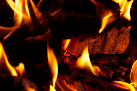 burning red wood, charcoal covered with fire