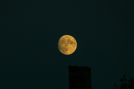 yellow moon in the dark blue background of the night sky
