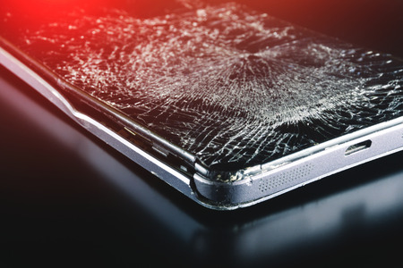 Broken phone on black background, phone repair advertisement
