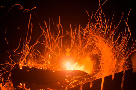 Burning firewood in the fireplace, coal background. Coal fire with sparks