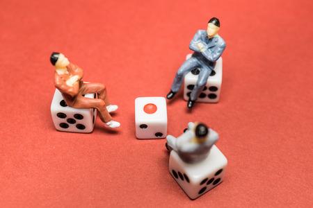 Three men sit on the dice