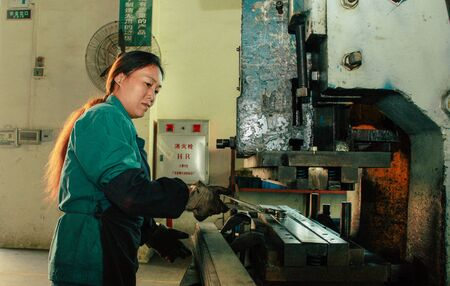 Chinese worker working on the machine 報道画像