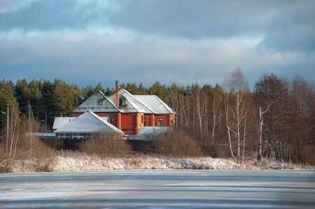 Russian winter landscape with a residential country house on the shore of a frozen pond