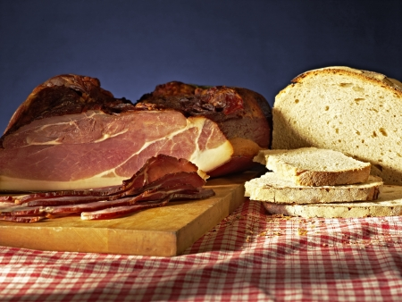 black forest ham slices snack with bread on wooden board and blanket photo