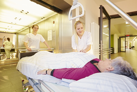 Nurses with bed in front of elevator Stockfoto