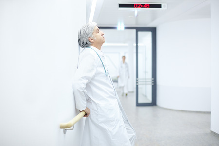 doctor burnout: leaning against the wall in the hospital sleeping doctor Stock Photo