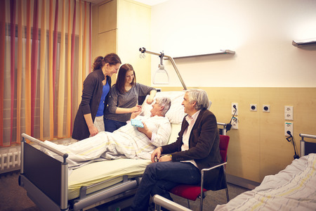 Hospital visit family with patient in bed