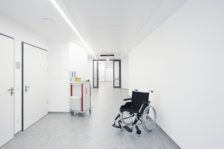 Wheelchair in the hallway with a door at the hospital Banco de Imagens