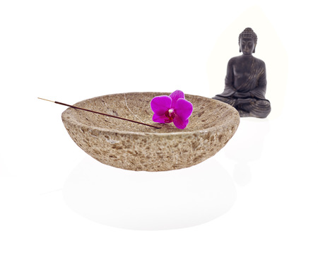 Buddha with bowl blossom of an orchid and joss stick photo